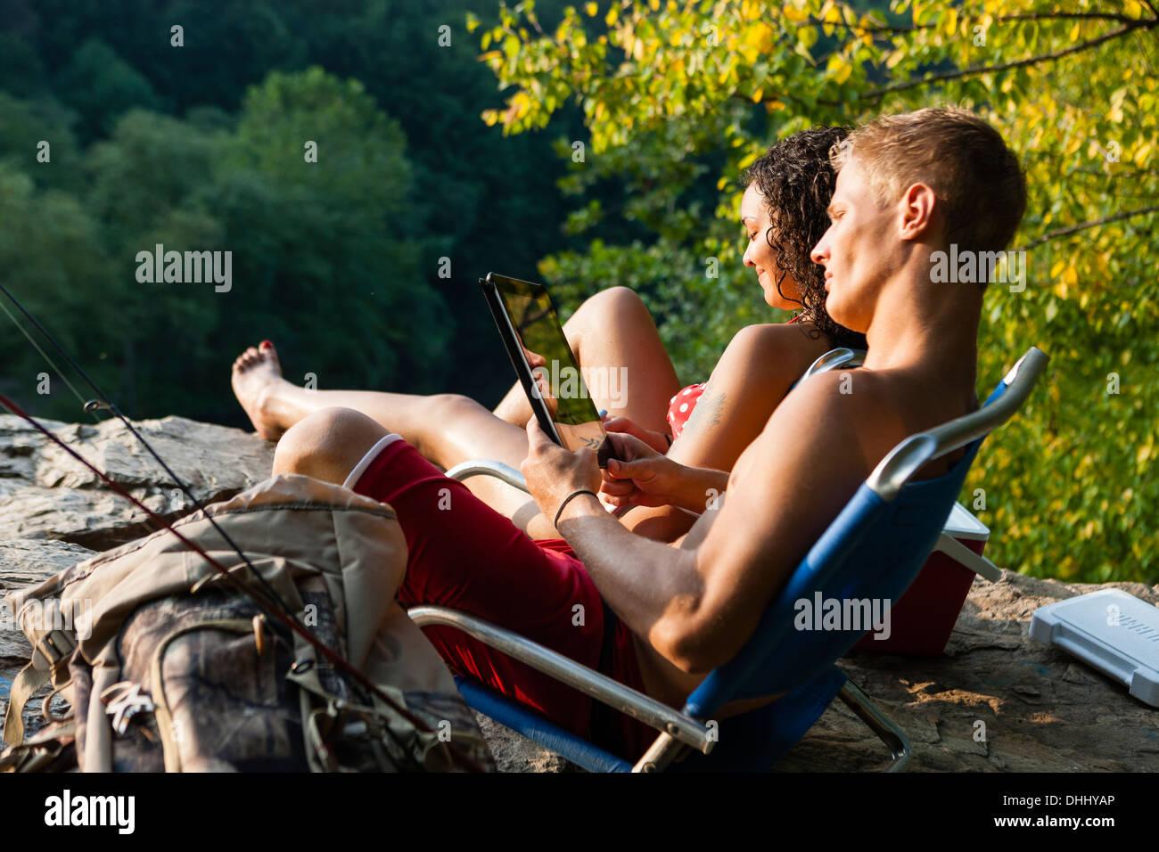 Young couple relaxing on rock ledge, Hamburg, Pennsylvania, USA - Stock Image