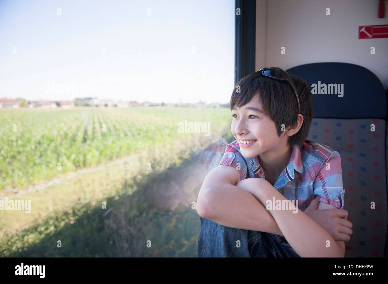 Boy looking out of train window - Stock Image
