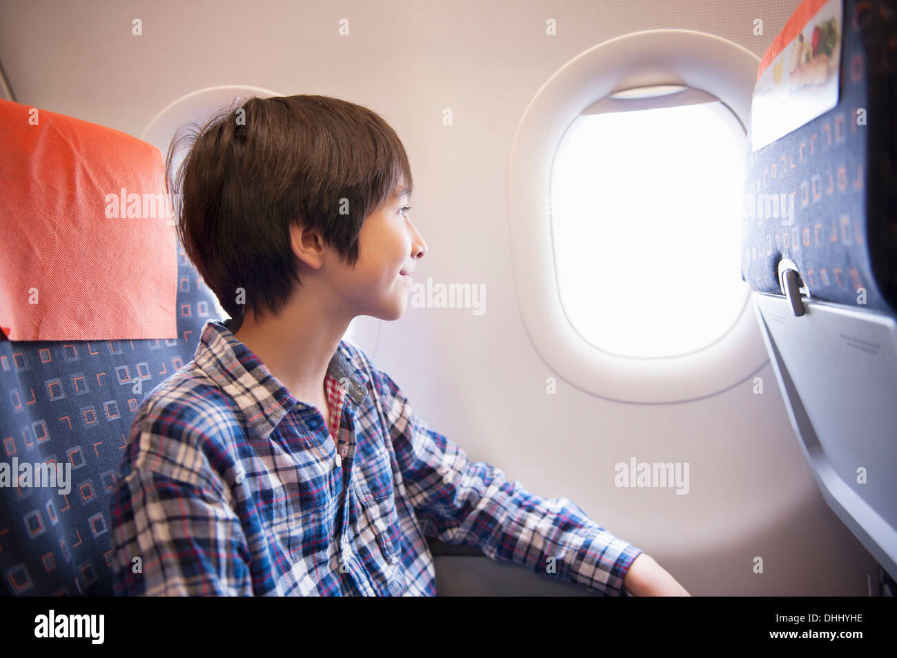 Boy looking out of window on aeroplane Stock Photo
