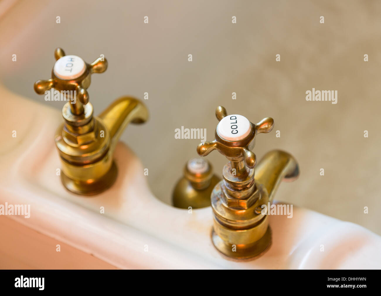 Old brass bath taps with hot and cold engraved on tops - Stock Image