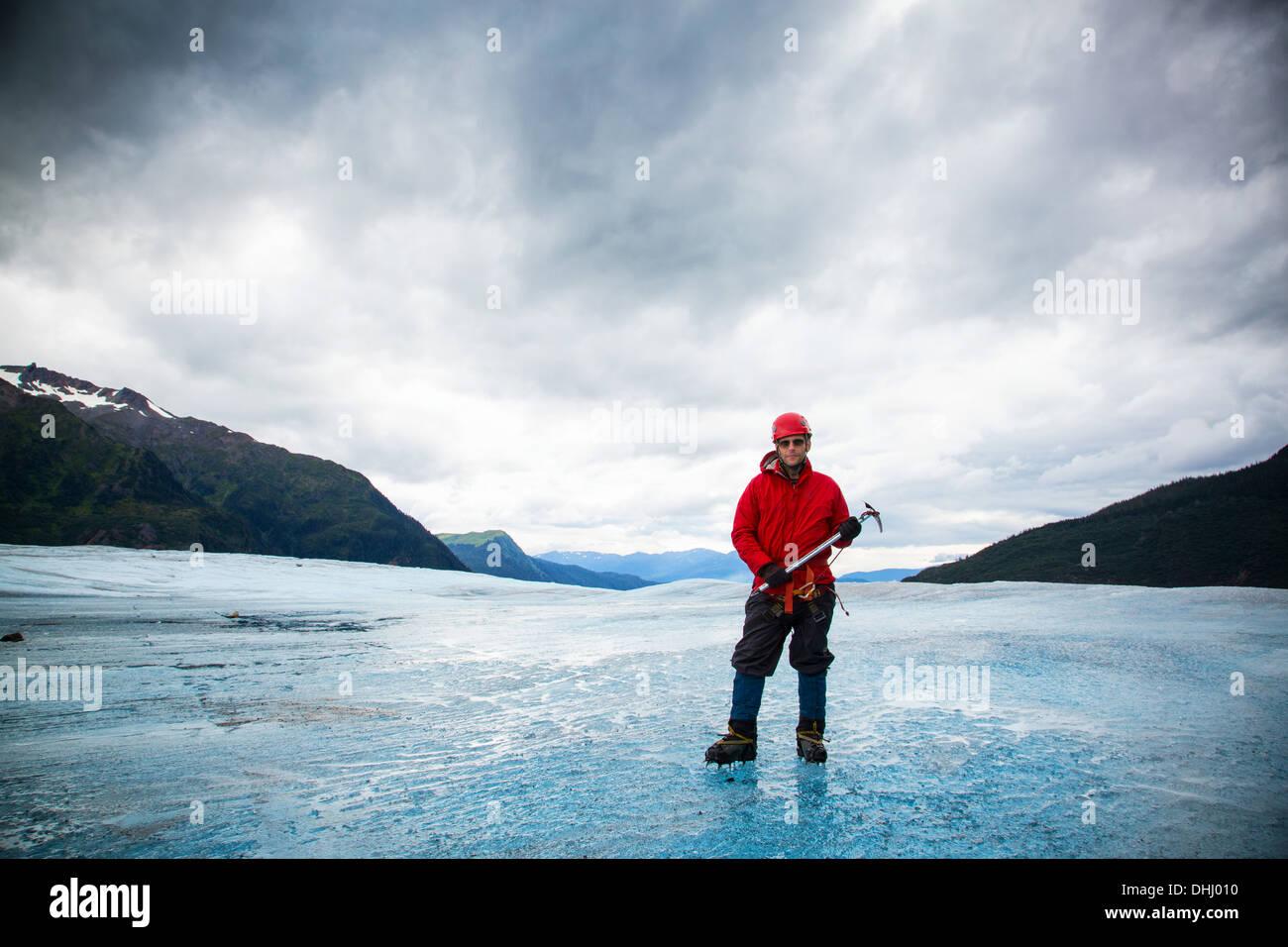 Man with ice pick on Mendenhall Glacier, Alaska, USA - Stock Image