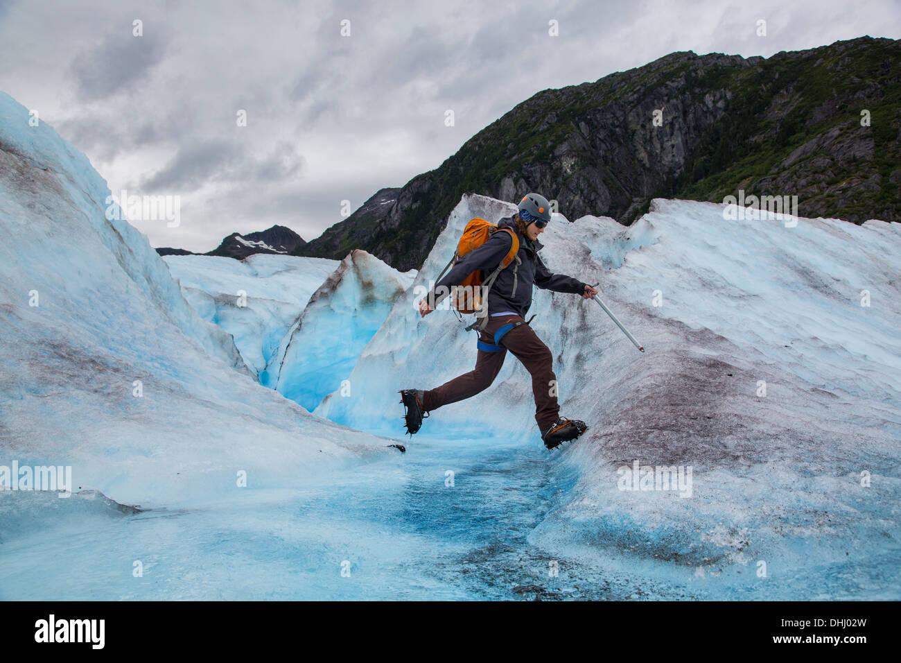 Young man walking on Mendenhall Glacier, Alaska, USA - Stock Image