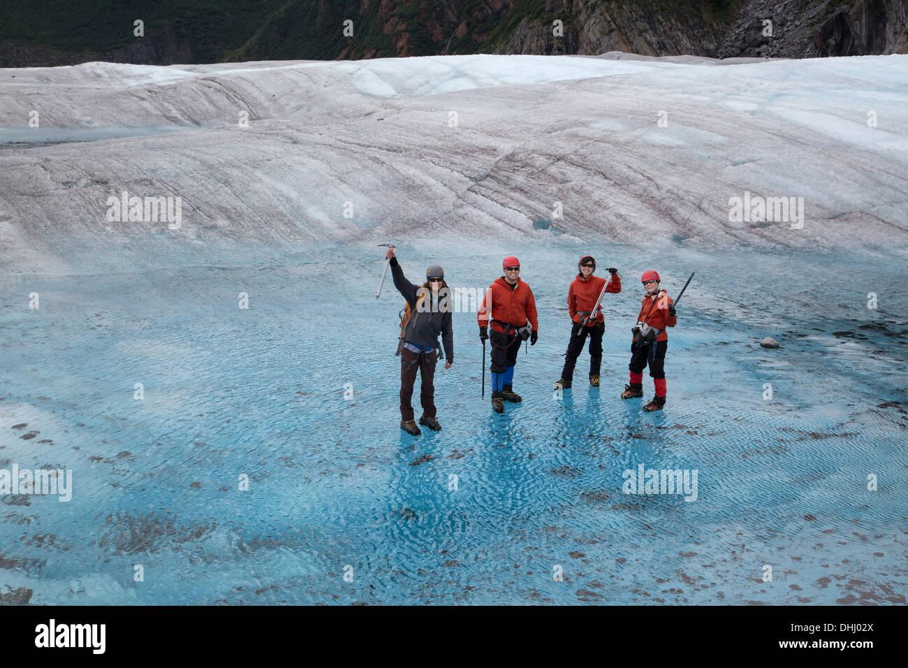 Four people standing on Mendenhall Glacier, Alaska, USA - Stock Image