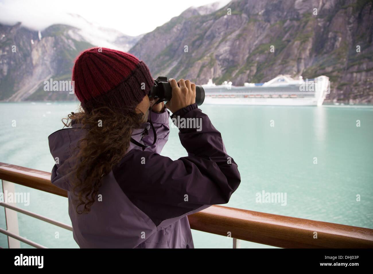 Woman using binoculars on cruise ship, Ketchikan, Alaska, USA - Stock Image