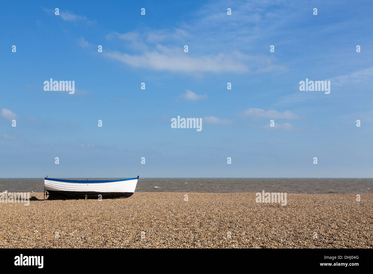 Aldeburgh beach in Suffolk, East coast of England, Uk with old wooden boat on the shingle - Stock Image