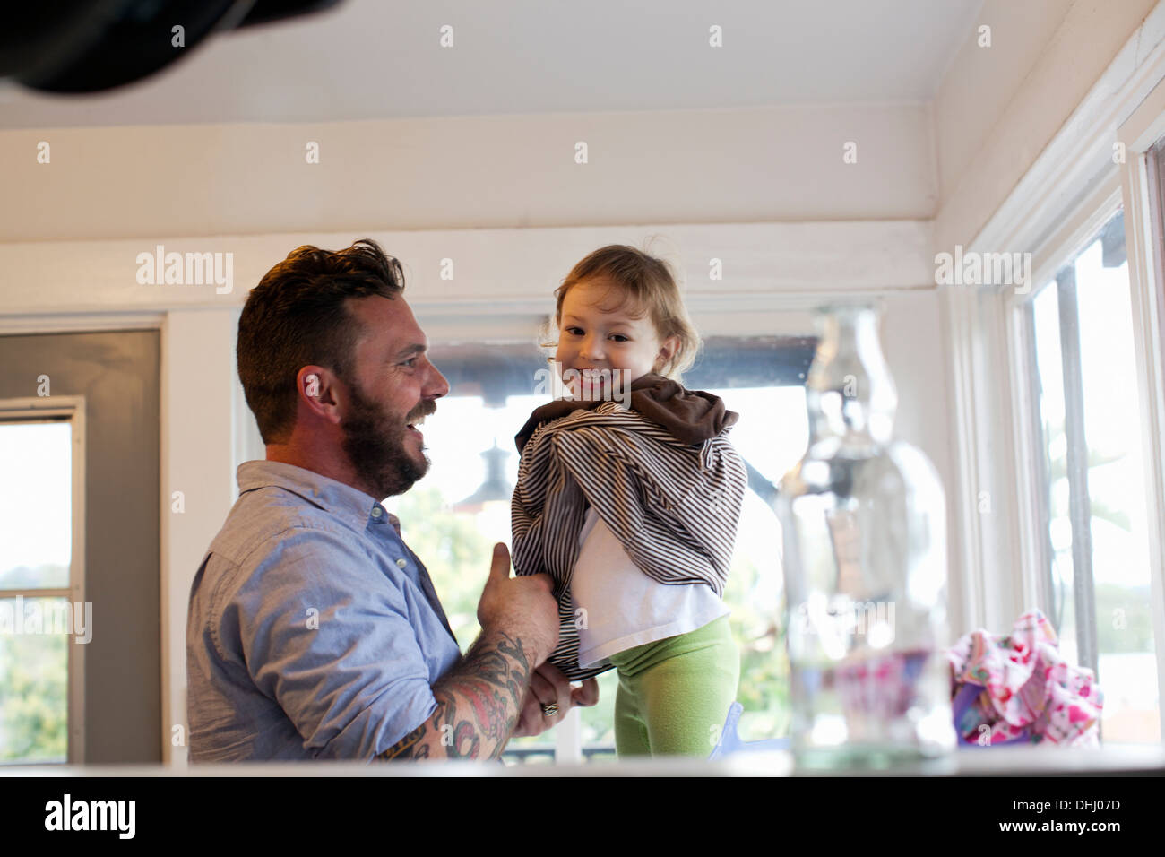 Father getting daughter dressed - Stock Image