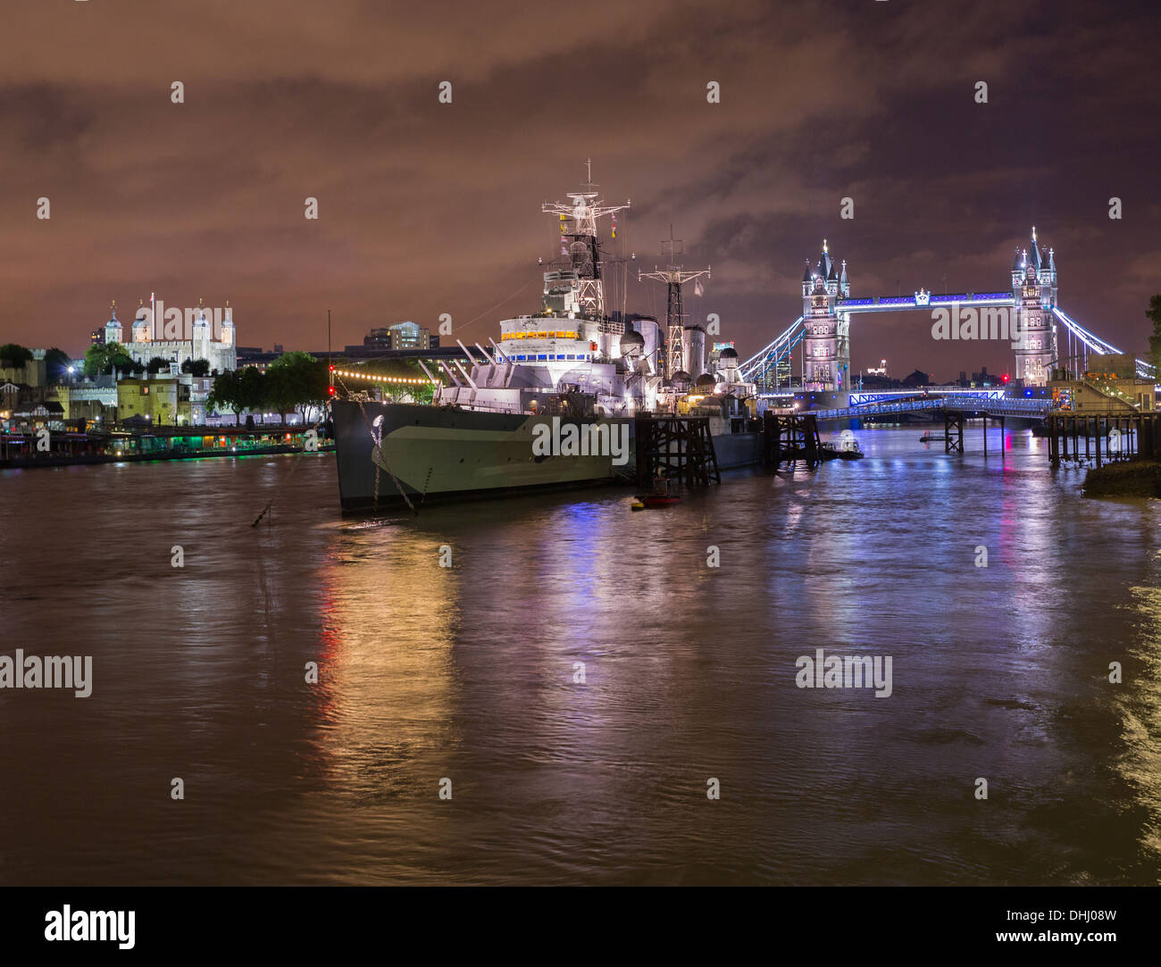 HMS Belfast, Tower Bridge and Tower of London on River Thames, London, UK at night - Stock Image