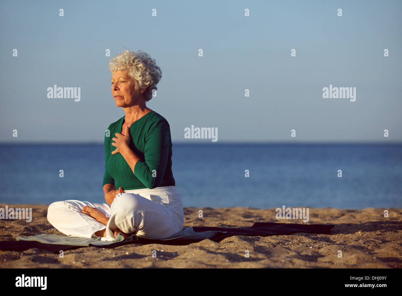 Senior woman in meditation by beautiful ocean. Eldery woman doing yoga on beach. - Stock Image