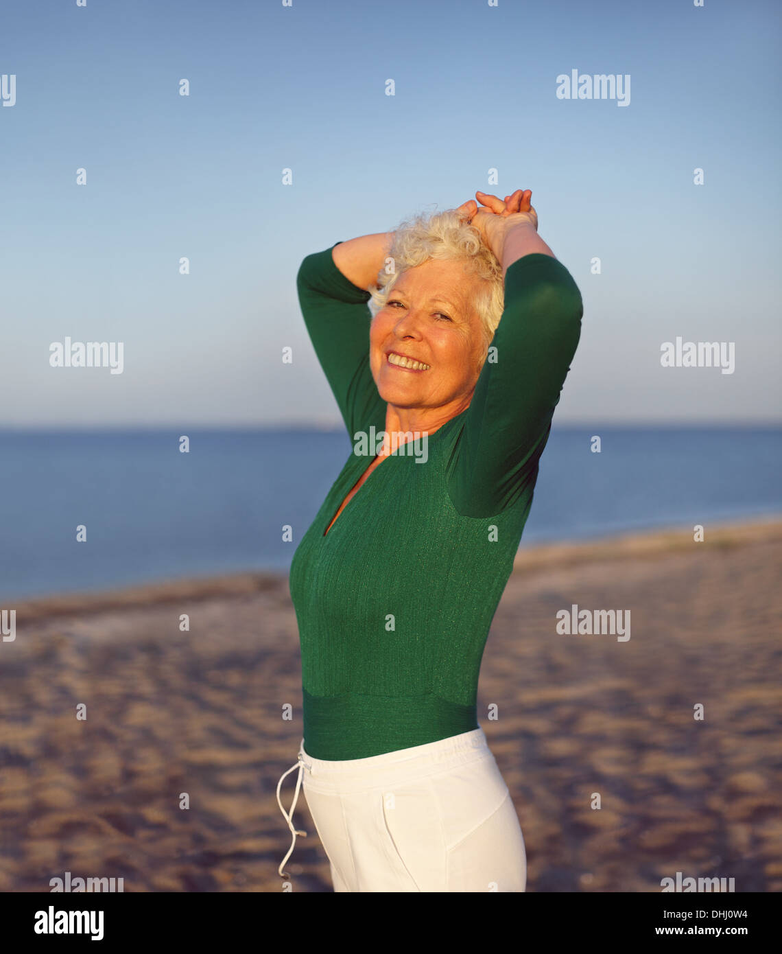 Happy elder woman looking relaxed on the beach with her hands on her head. Active senior female on the beach relaxing - Stock Image