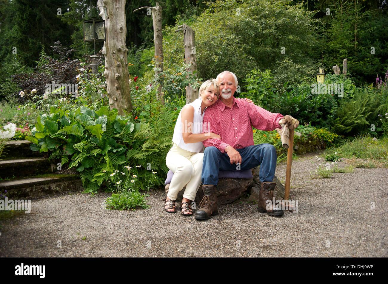 Portrait of senior couple sitting in garden Stock Photo