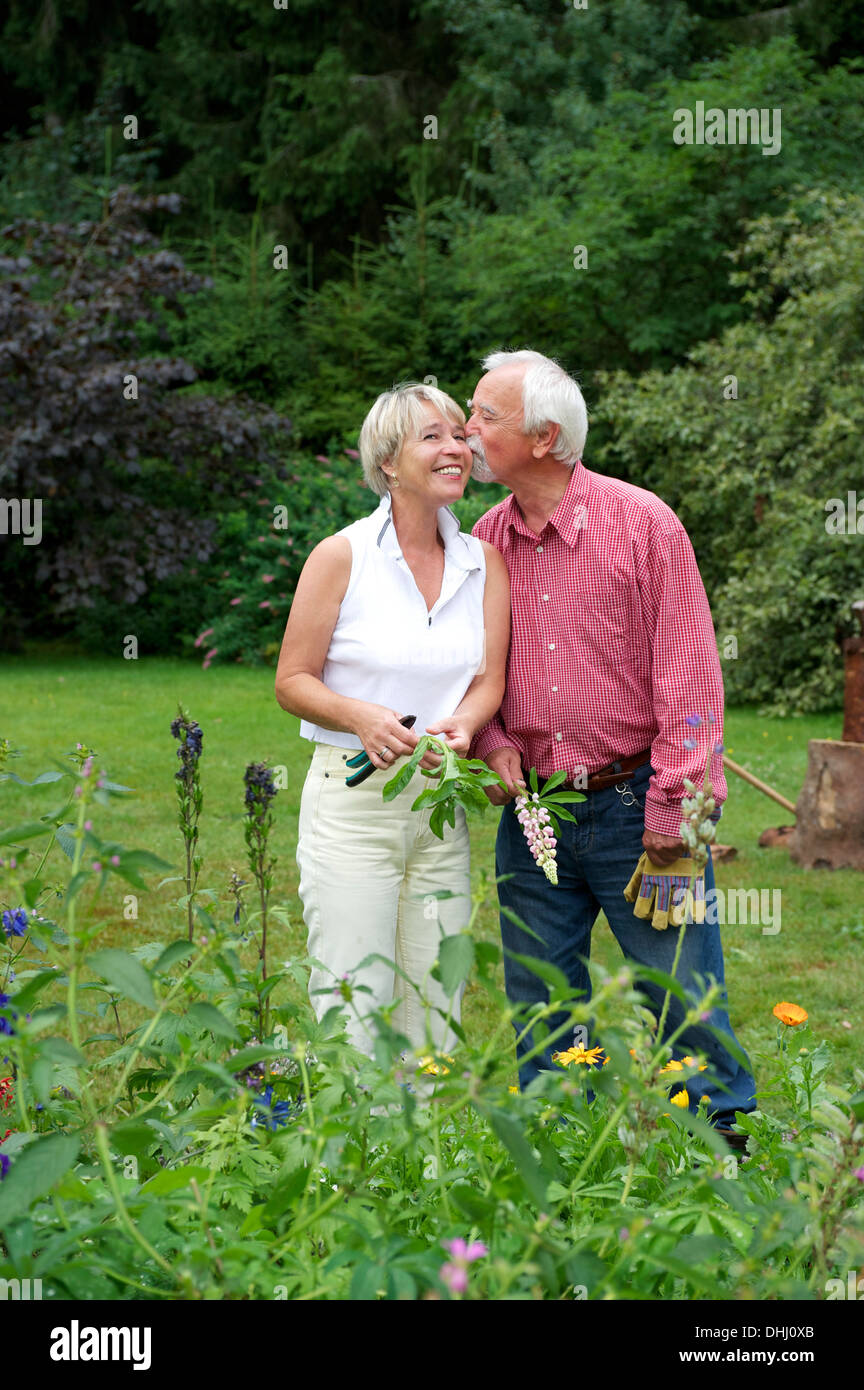Portrait of senior couple sharing a kiss in garden - Stock Image
