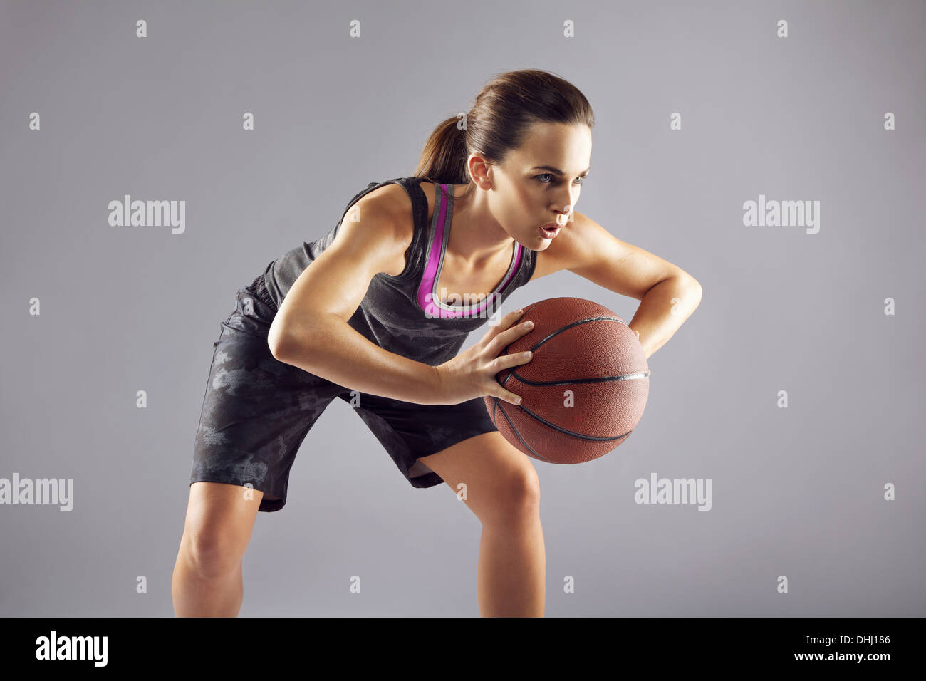 Young female basketball player in uniform passing a basketball. Woman in sportswear playing basketball and looking away on grey - Stock Image
