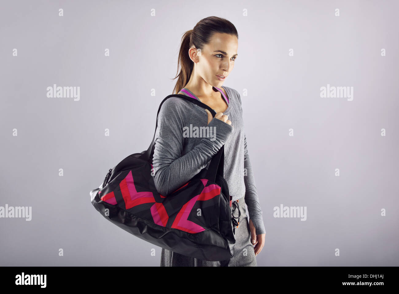 c2dbaa5b Portrait of fit young woman carrying gym bag looking away at copyspace over  grey background. Beautiful caucasian female