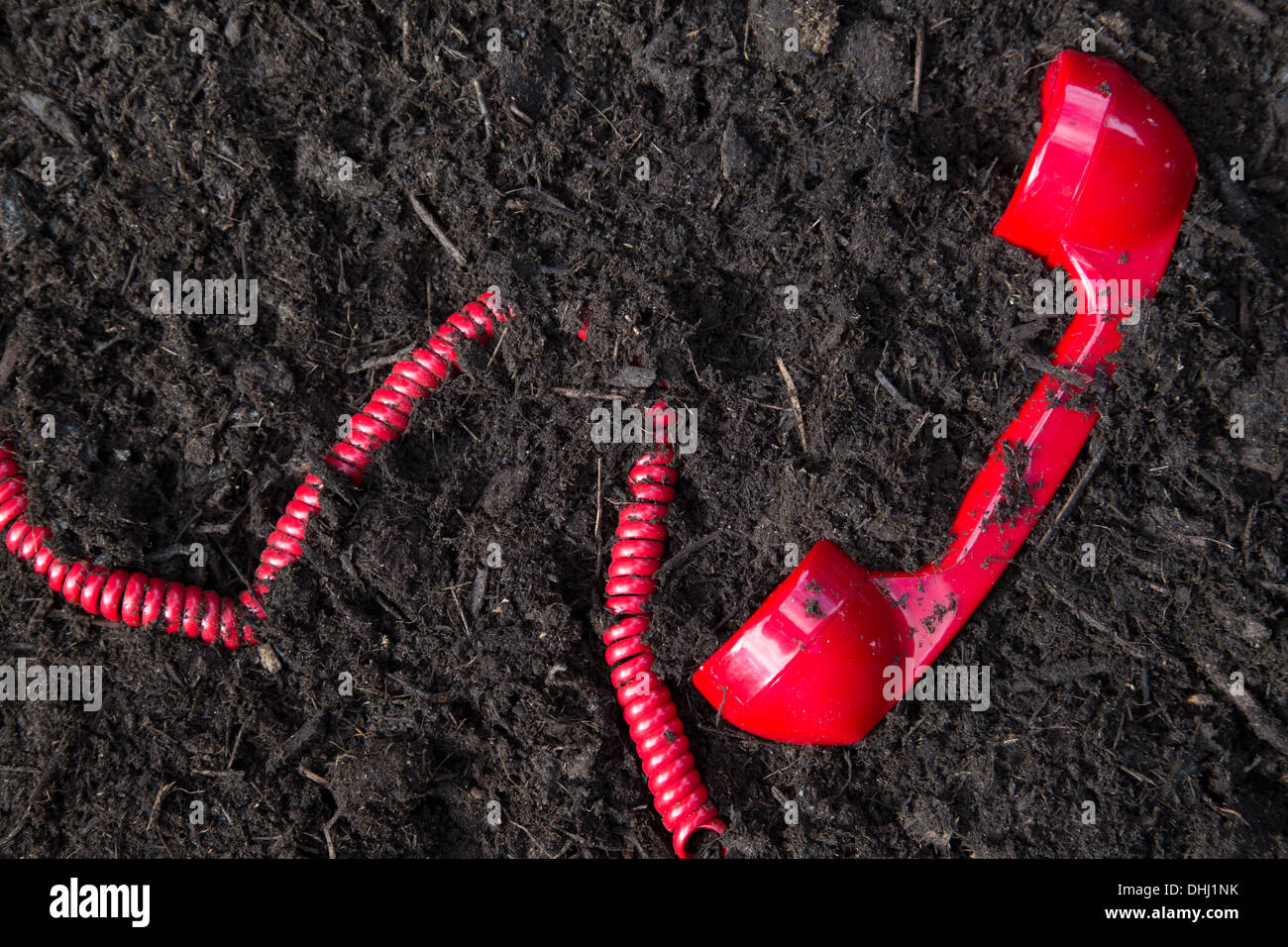 Red retro telephone handset buried in soil - Stock Image
