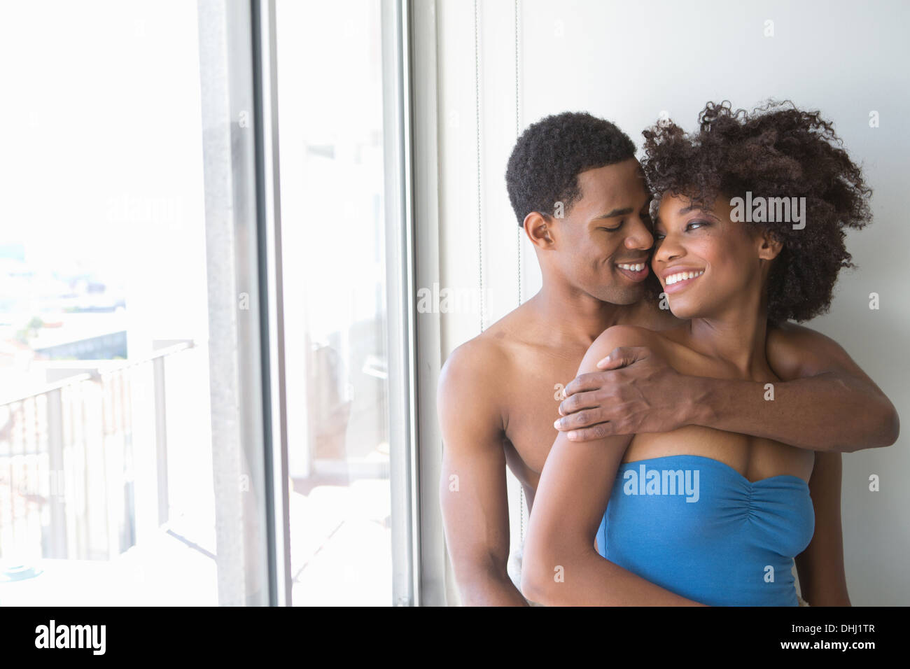 Portrait of young couple by window, man with arm around woman - Stock Image
