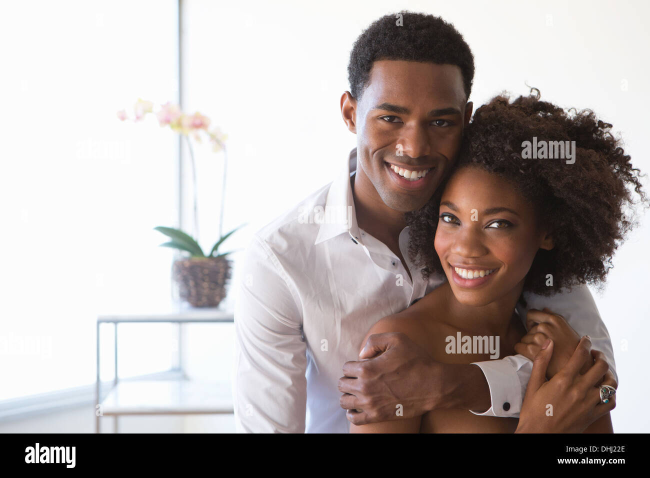 Portrait of young couple, man with arm around woman - Stock Image