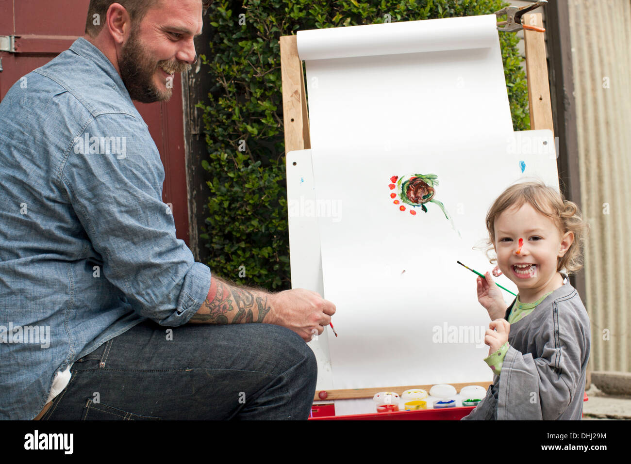 Father fooling around putting paint on daughter's face - Stock Image