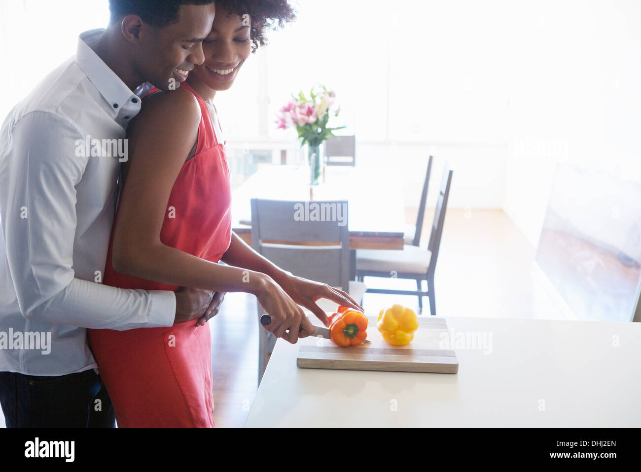 Young woman chopping peppers, man with arms around her - Stock Image