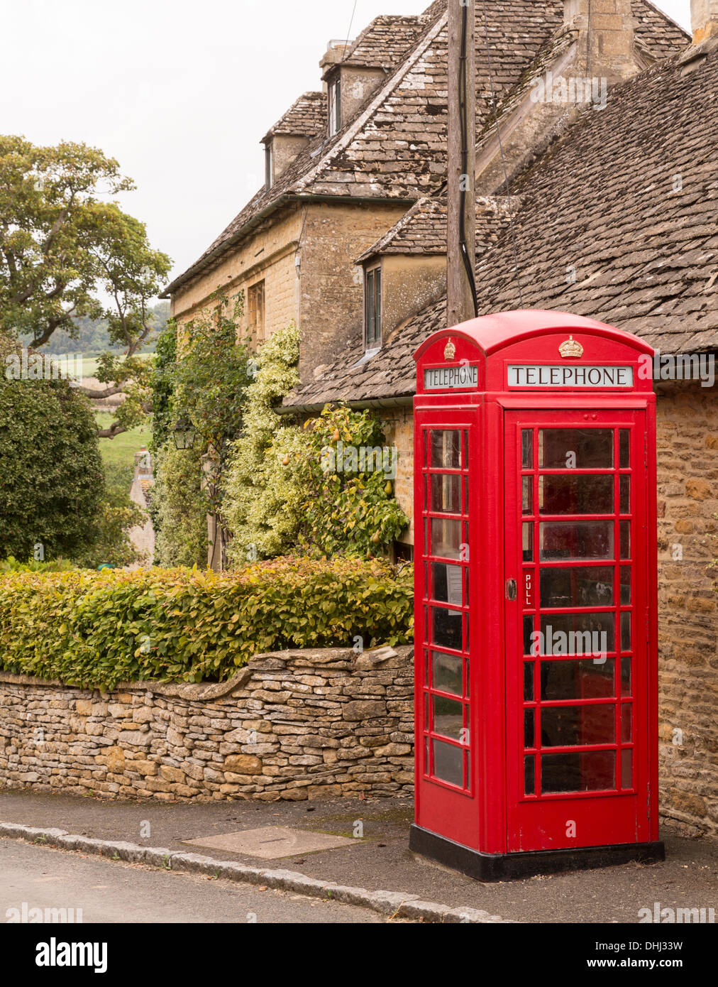 Red telephone box in Cotswold village, England, UK - Stock Image