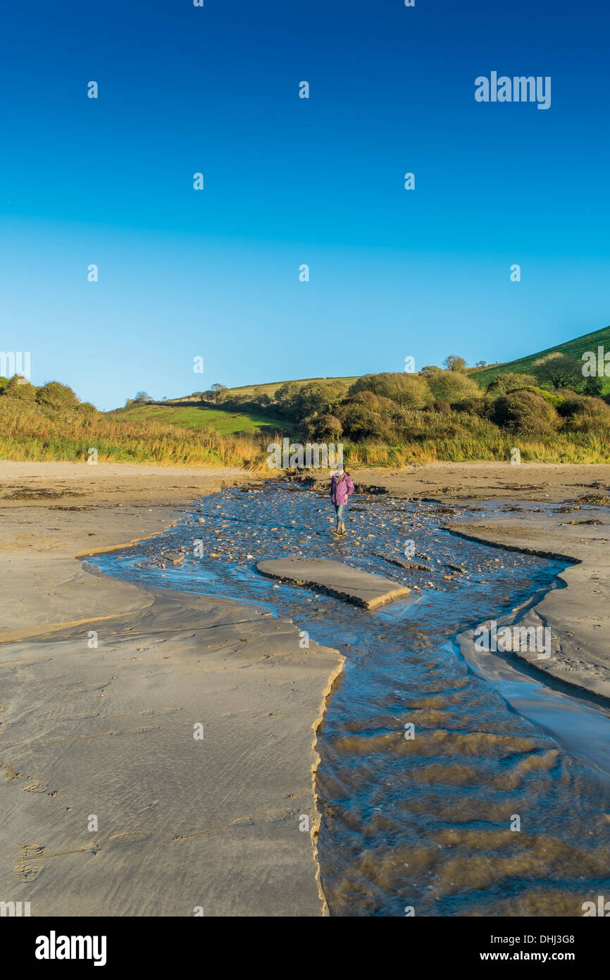 Walker crossing a stream flooding onto a beach after heavy rains. Wonwell, South Devon. UK - Stock Image