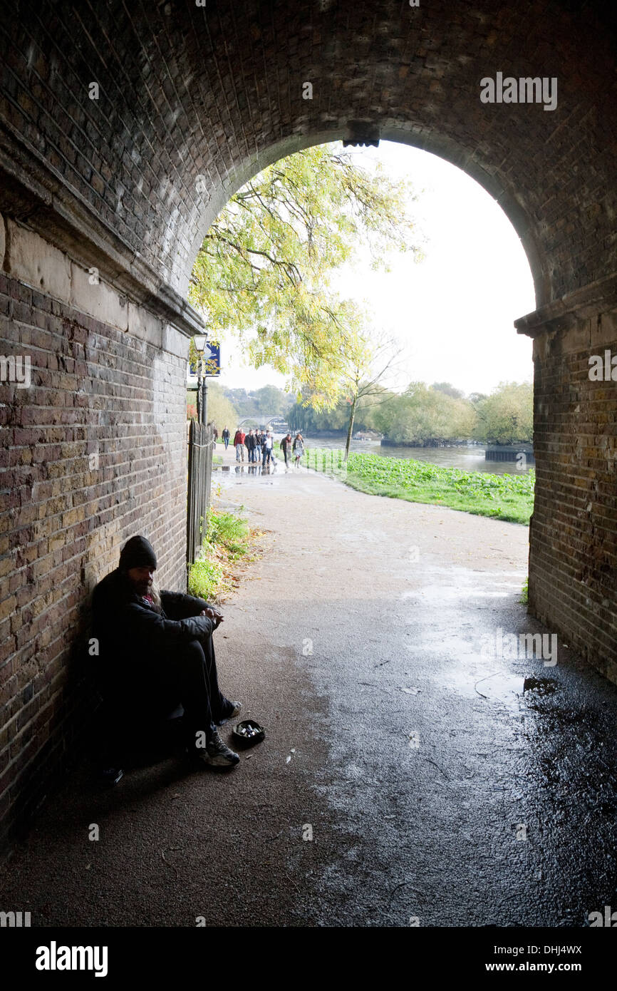 A homeless man begging in London under the bridge on the Thames path at Richmond, london UK - Stock Image