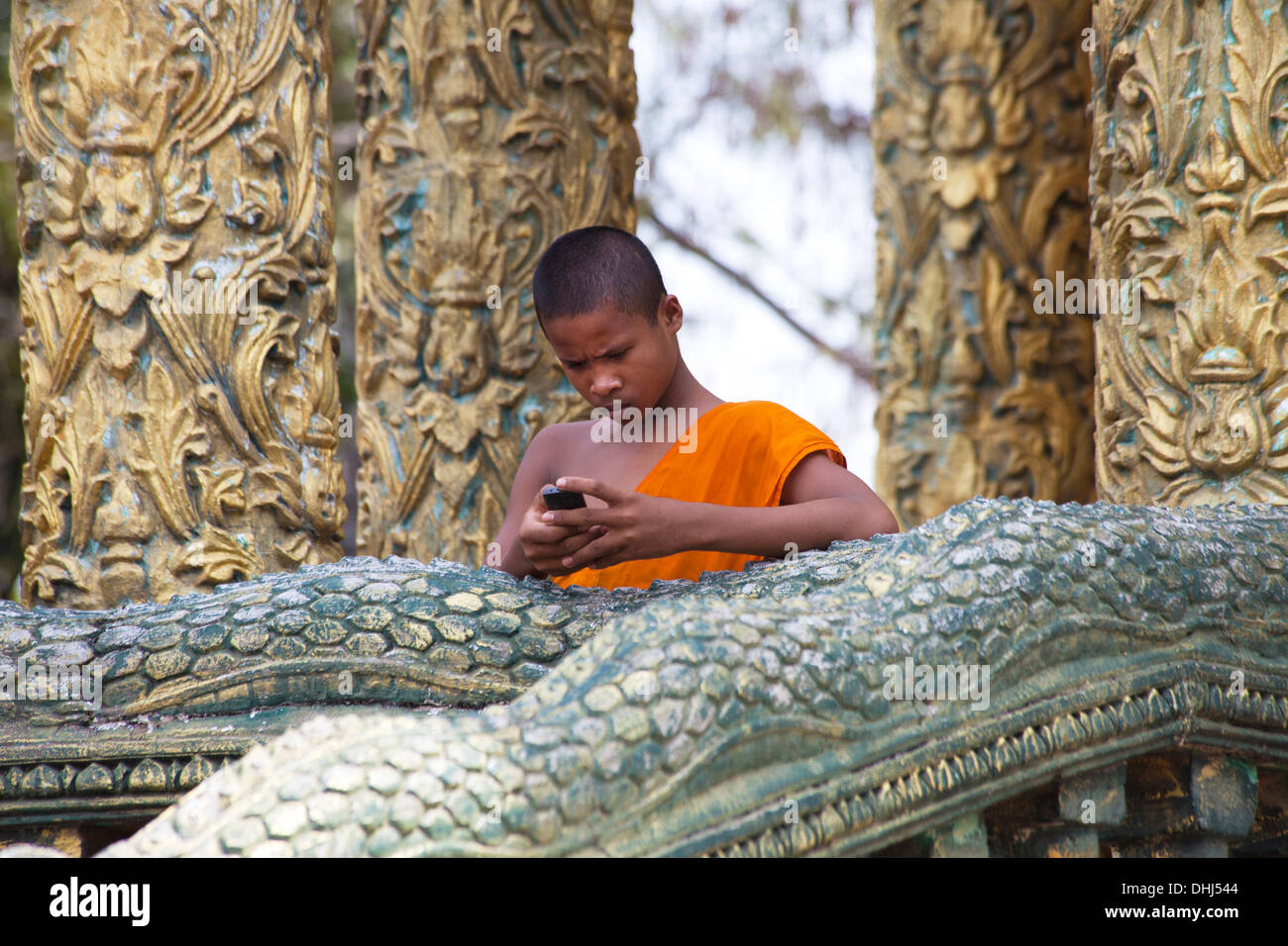 Young buddhistic monk with a mobile phone in a temple in the Kam, Cambodia, Asia - Stock Image