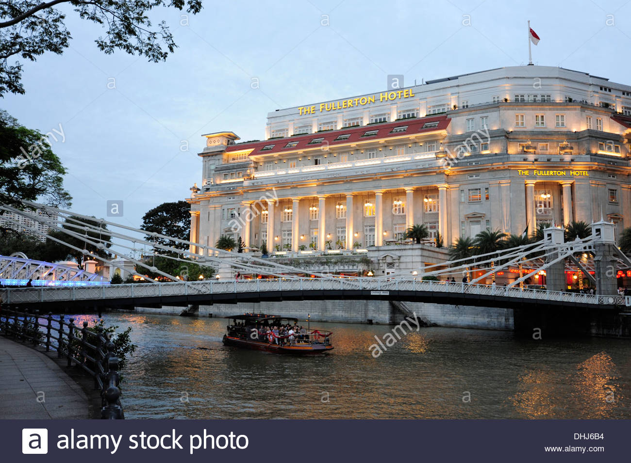 Cavenagh bridge crossing the Singapore River, in the background The Fullerton Hotel at dusk, Singapore, Asia - Stock Image