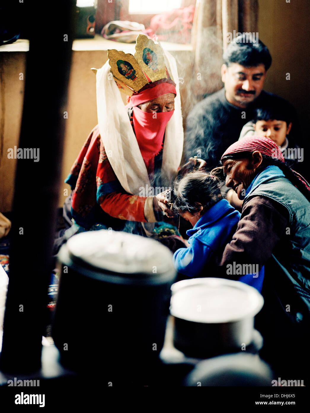 Oracle of Sabu, 77 year old healer Sonam Sangmu is treating a child in her kitchen near Leh, Ladakh, Jammu and Kashmir, India - Stock Image