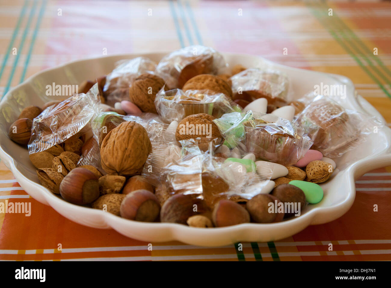 Dry nuts chocolate sugared sweets offer wedding gift snack guests offered disk plate ceremony church tokens appreciation invite - Stock Image
