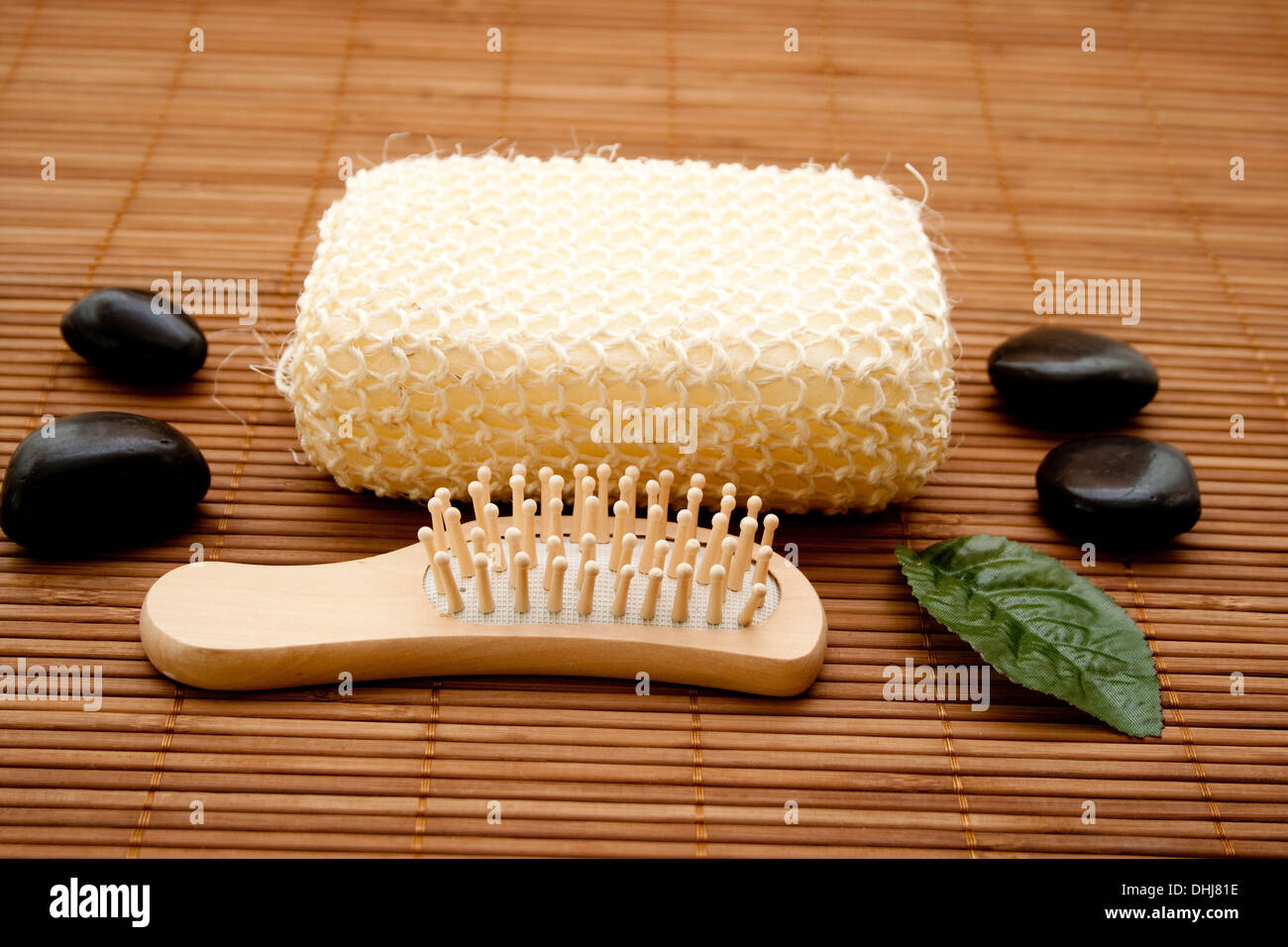 Hairbrush with massage sponge on brown wooden base - Stock Image