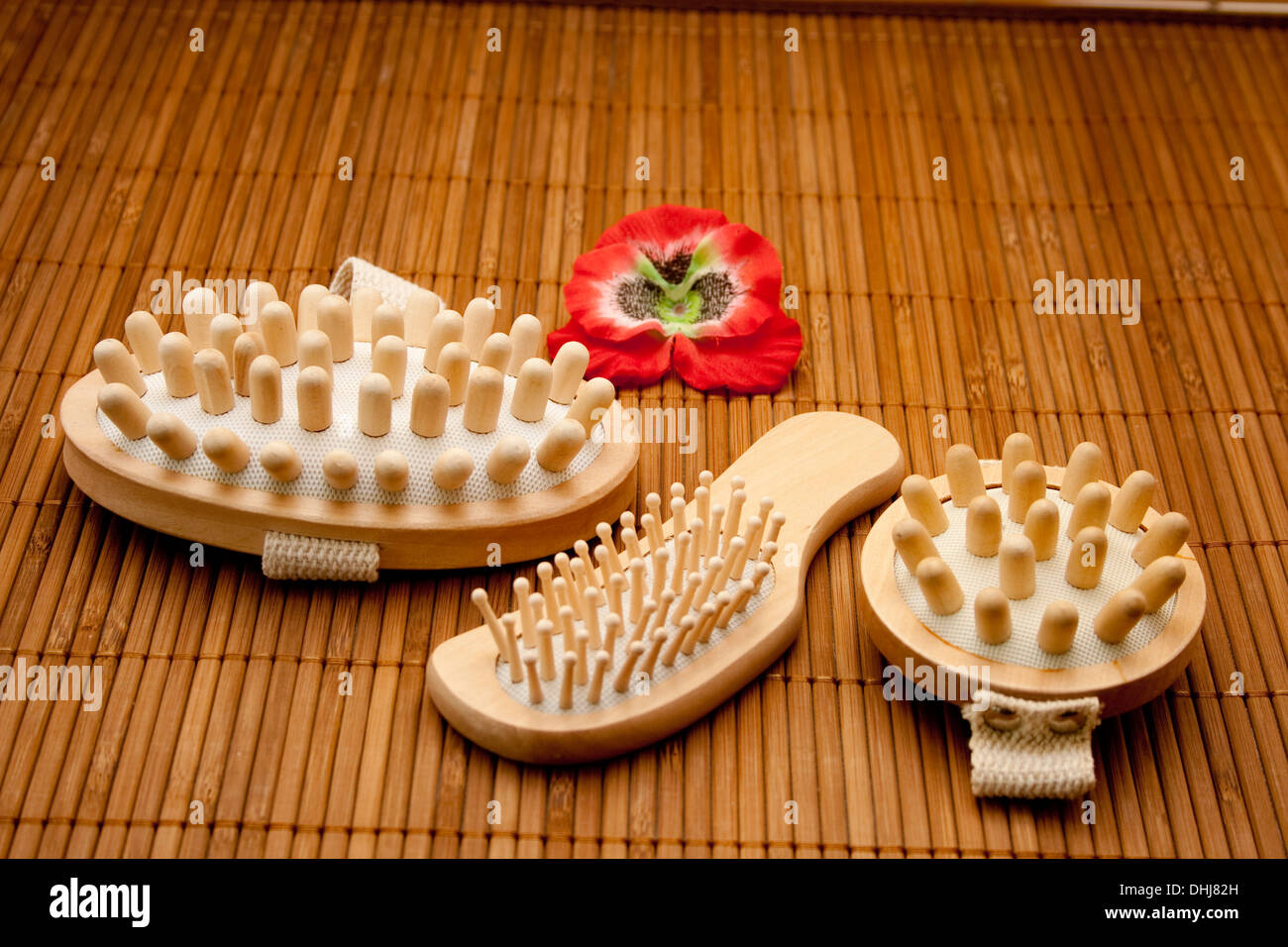 Hairbrush with massage brush on brown wooden base - Stock Image