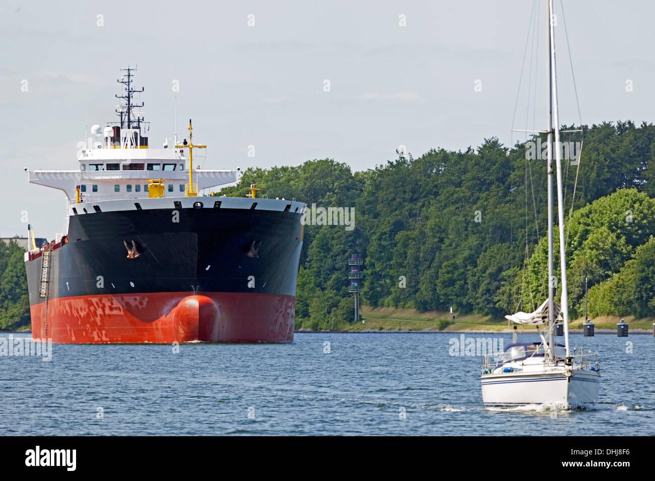 Tanker ship and sailboat on Kiel Canal, Germany - Stock Image