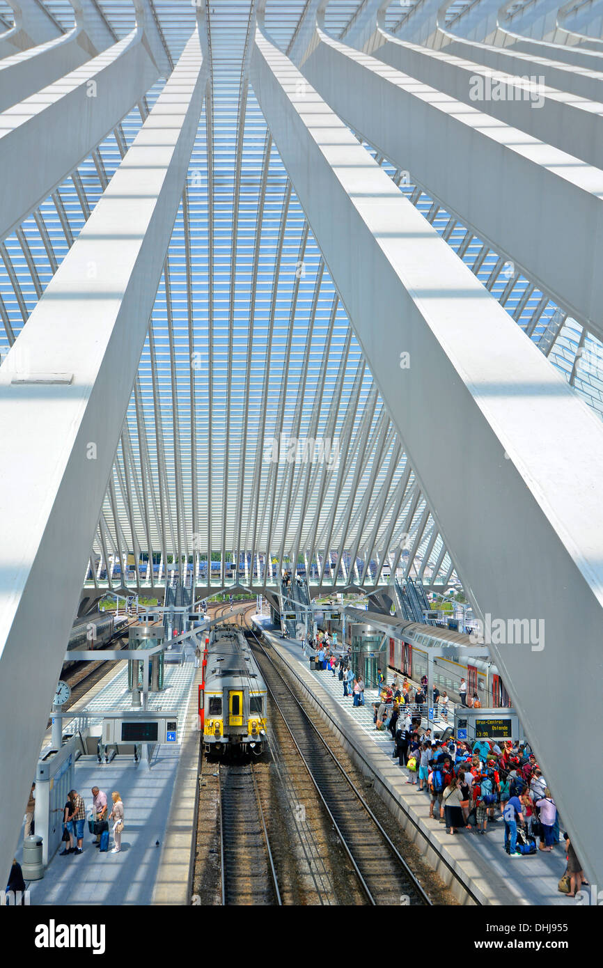 Public transport aerial view from above looking down between beam Belgium passenger train & Liege station platform people waiting under glass roof - Stock Image