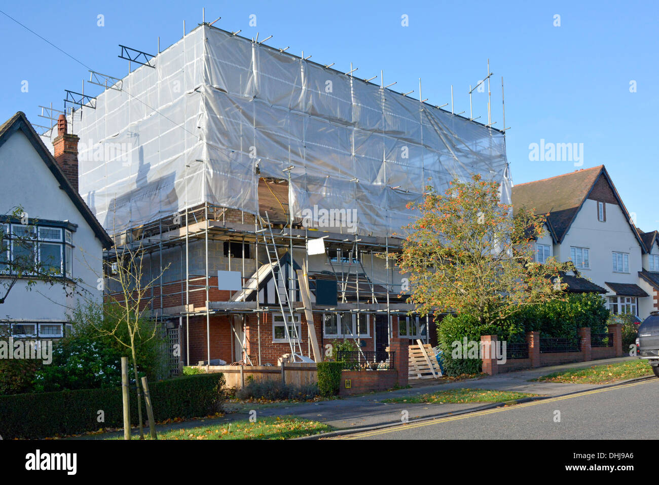 Detached house cocooned inside protective plastic sheeting during structural alterations - Stock Image