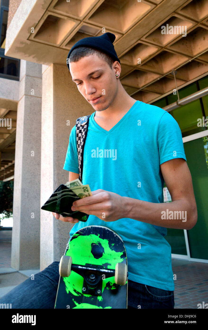 A young man with a wallet and money on a college campus. Stock Photo