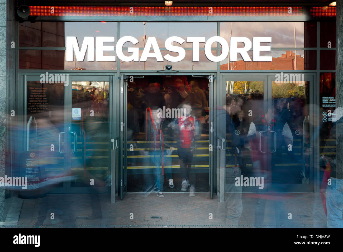 Fans of Manchester United Football Club enter and exit the club's Old Trafford Megastore (Editorial use only). - Stock Image