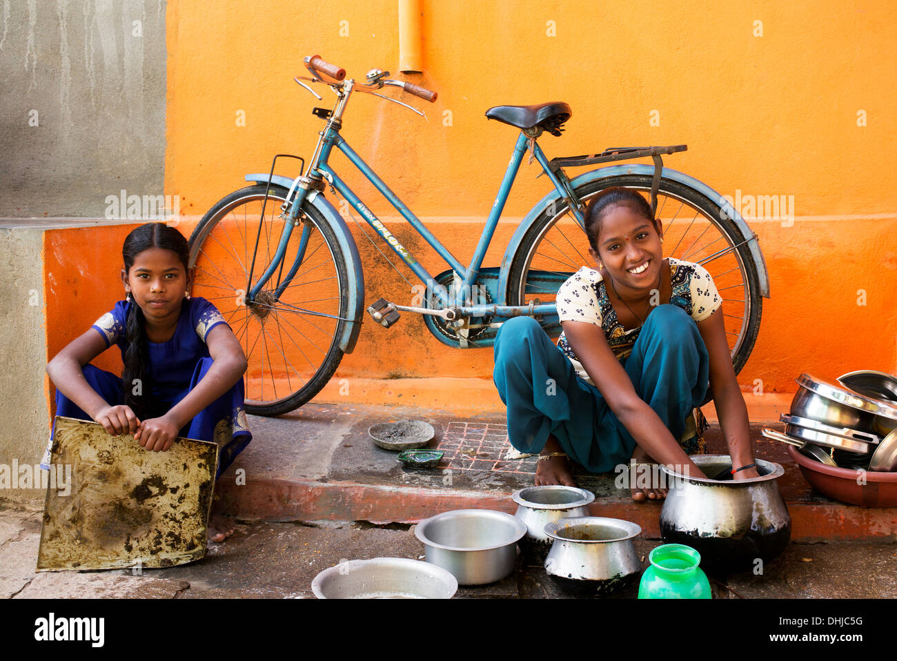 Indian teenage girl washing dishes outside their rural indian village home. Andhra Pradesh, India - Stock Image