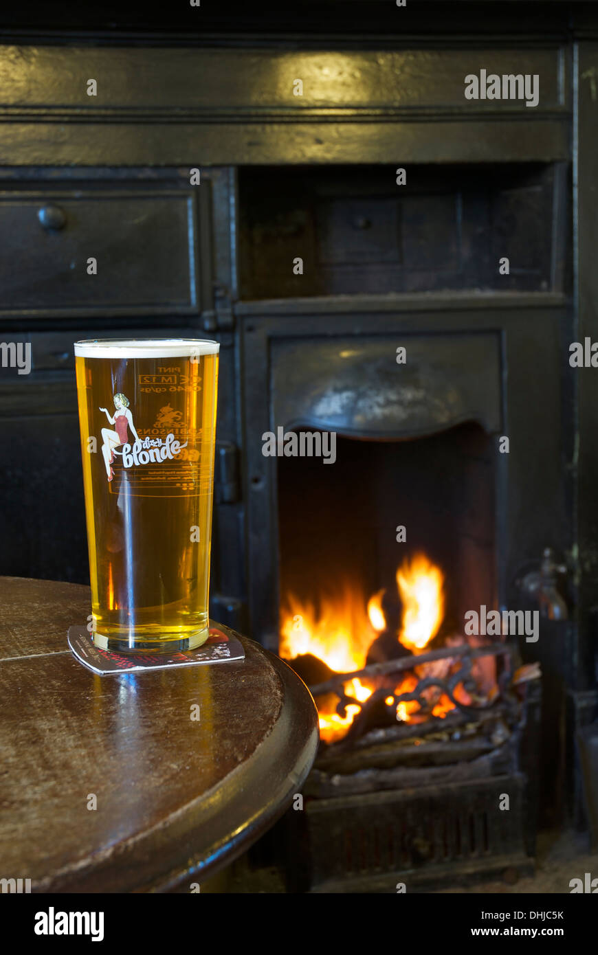 A pint of Robinson's Dizzy Blonde pale beer, in a pub with an open fire - Stock Image
