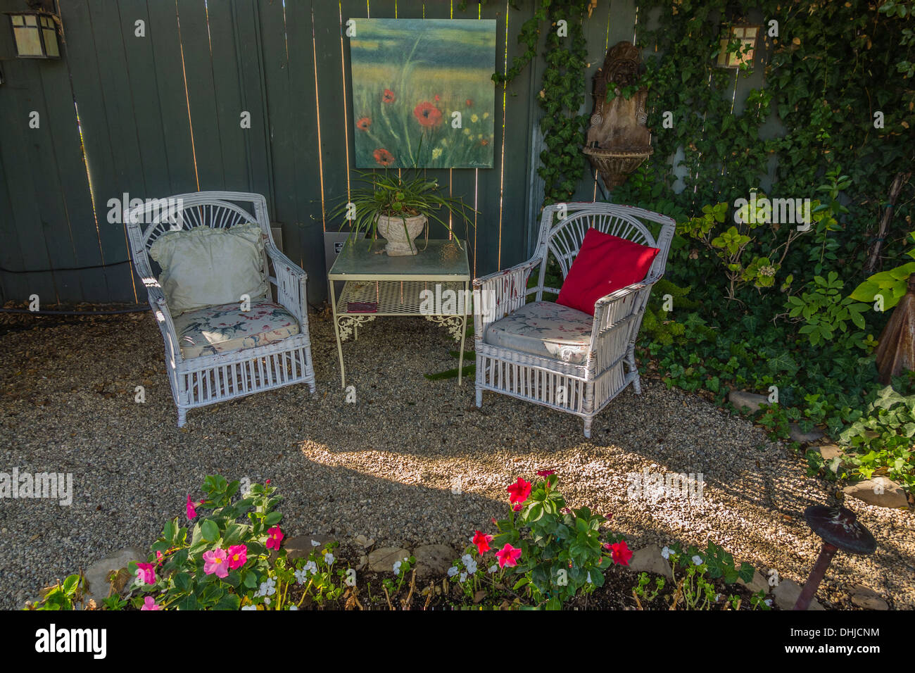 Two white garden chairs are placed next to a table and a ...