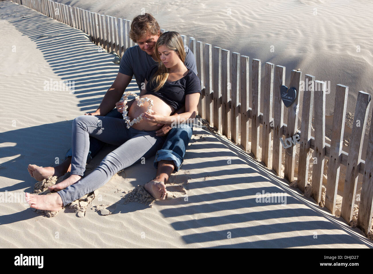 A pregnant woman and her partner sitting on the beach - Stock Image