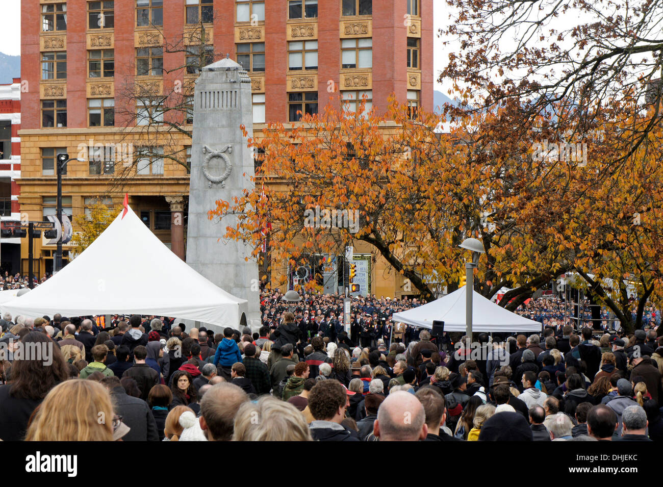 People gather at the Remembrance Day ceremonies at the Victory Square Cenotaph in downtown Vancouver, British Columbia, Canada - Stock Image