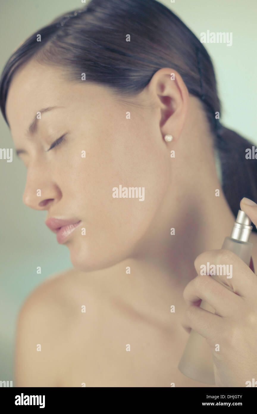 A young brunette woman spraying perfume on her neck - Stock Image