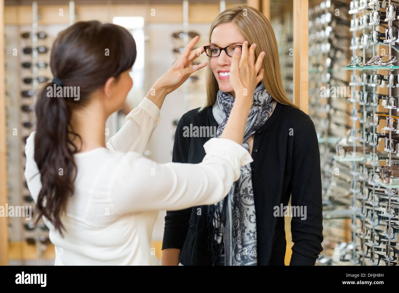 Salesgirl Assisting Customer To In Wearing Glasses - Stock Image