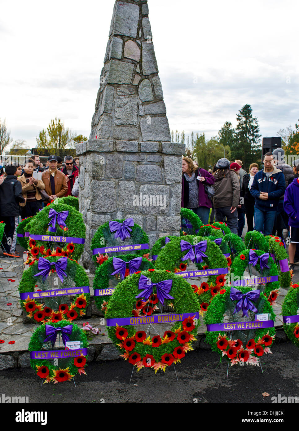 BURNABY, BRITISH COLUMBIA, CANADA – Monday November 11, 2013:  People observing the cenotaph decorated with wreaths and poppies following the Remembrance Day service in Confederation Park, Burnaby, BC. Canada.  Hundreds of people from the community gathered for the annual ceremony, to show respect and thanks to war veterans past and present. - Stock Image