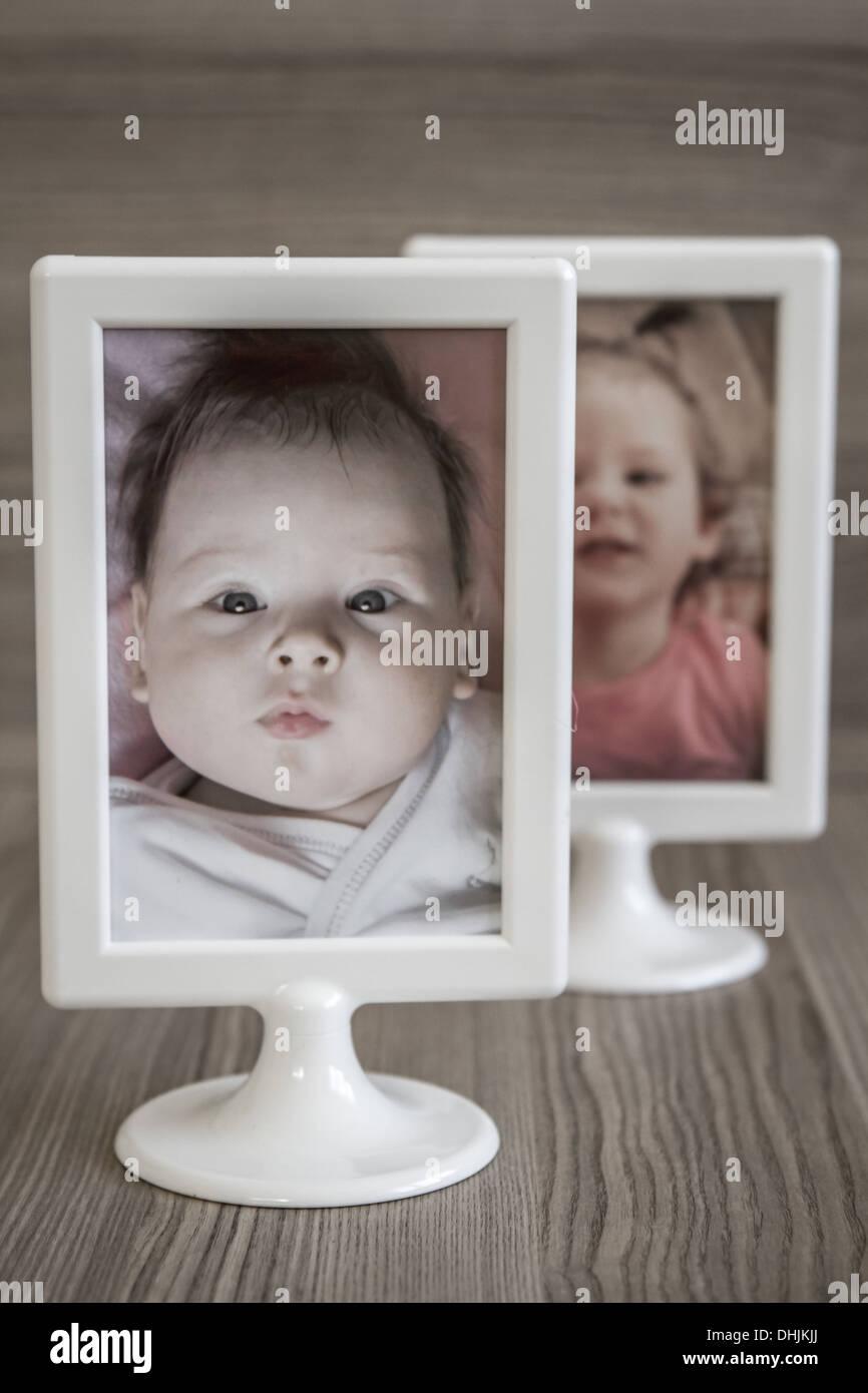 Children photos on plastic modern white frames on wooden background - Stock Image