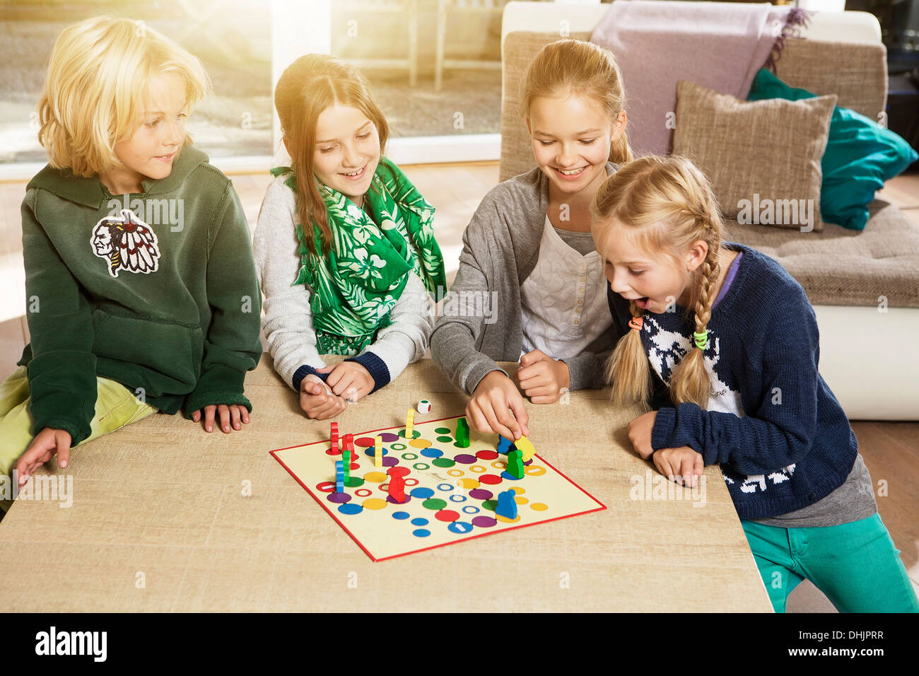 Four children playing ludo in living room Stock Photo