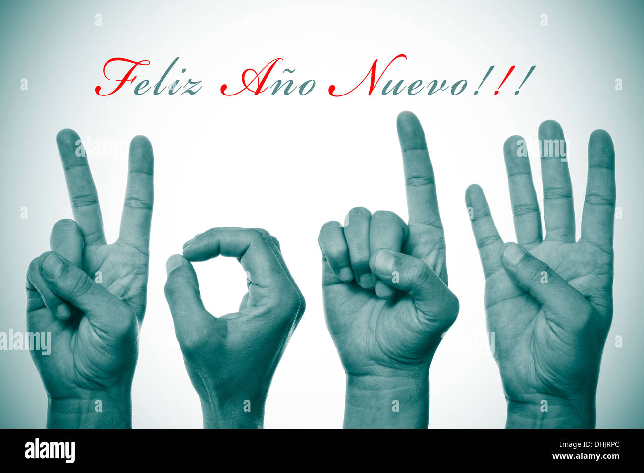 sentence feliz ano nuevo, happy new year written in spanish, and hands forming number 2014 - Stock Image