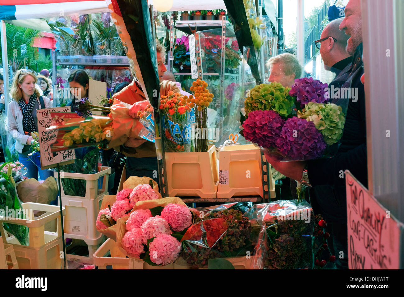 Customers buying flowers at Columbia Road flower market, East London, UK - Stock Image