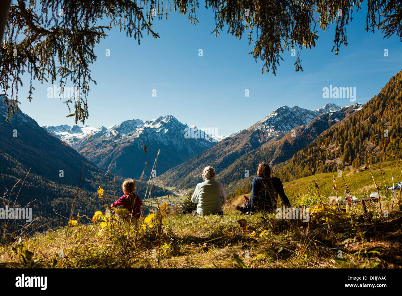 A family, two girls, a younger and an older woman sit on a meadow, autumn at Guarda, Engadin, Graubuenden, Grisons, Switzerland - Stock Image