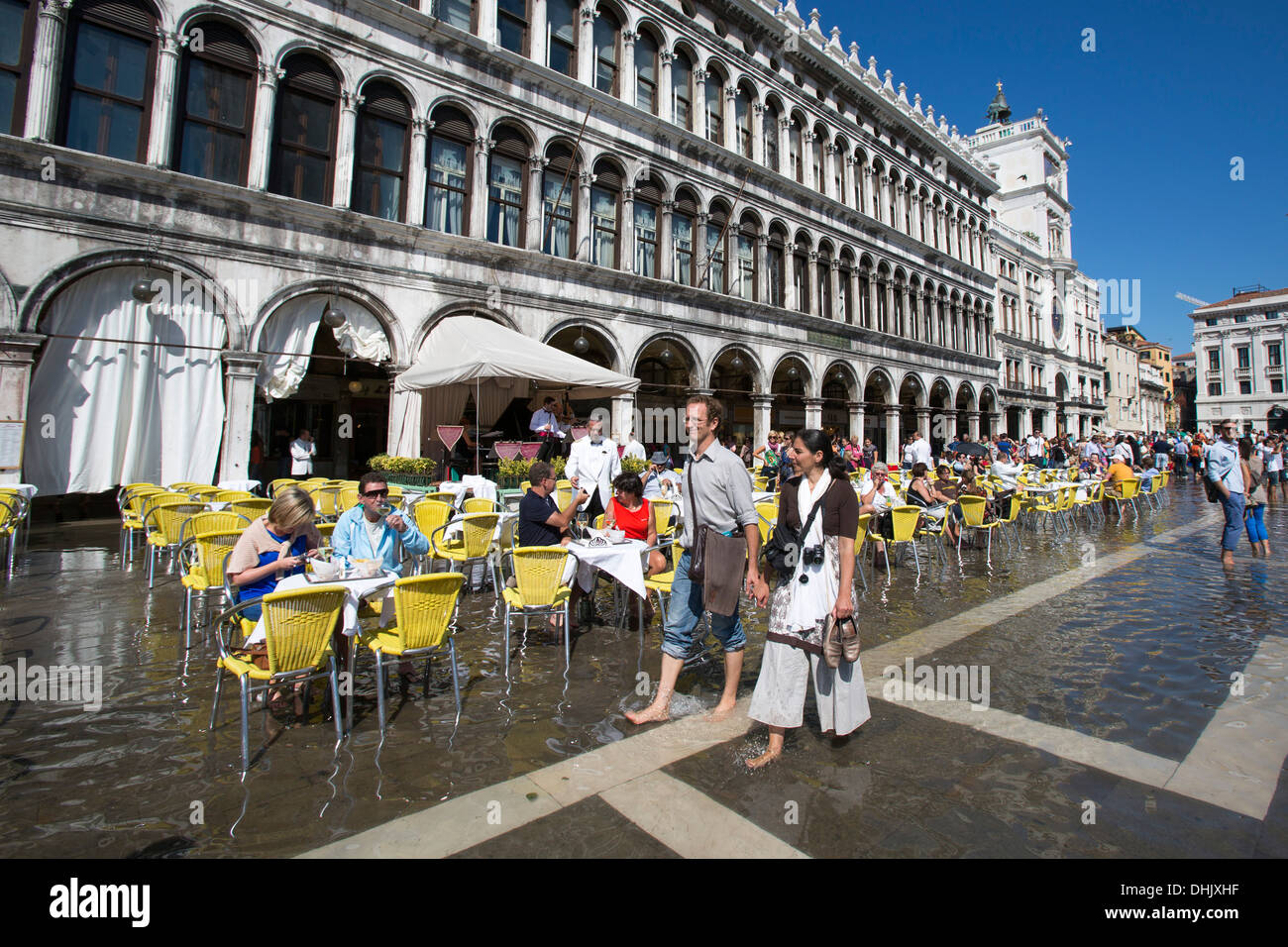 Young couple walking barefooted over flooded Piazza San Marco while people sitting outside of a cafe, Venice, Veneto, Italy, Eur - Stock Image